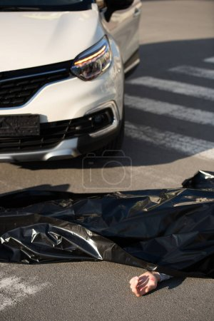 high angle view of corpse and car on road after traffic collision