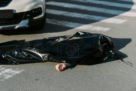 Photo pour Vue grand angle du cadavre et de la voiture sur la route après un accident de la circulation - image libre de droit