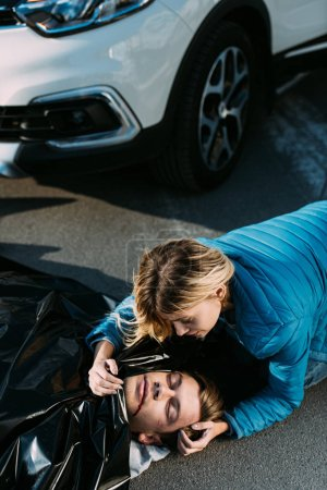 high angle view of young woman crying about dead man on road after traffic collision