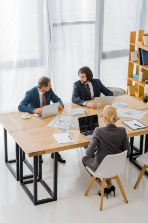 business people sitting at table and having discussion in office