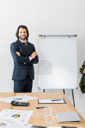 young smiling male insurance agent standing with arms crossed near white board in office