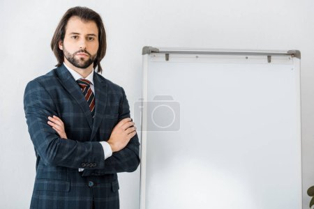 young serious male insurance agent standing with arms crossed near white board in office
