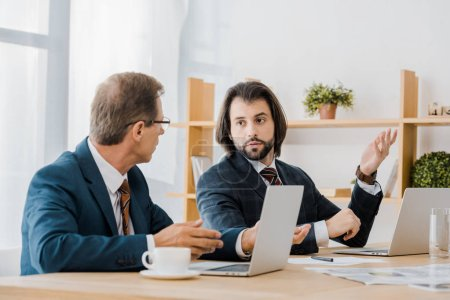 two adult men sitting at table and talking in insurance office