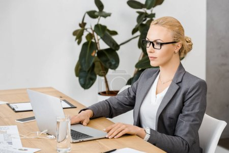 young woman in glasses sitting at table and using laptop in insurance office