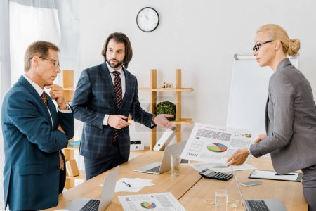 insurance workers standing near table and having discussion in office