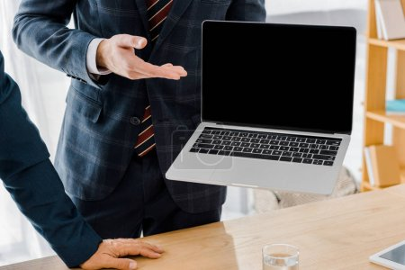 male insurance agent holding laptop with blank screen in office