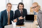 young smiling male insurance agent standing with workers and pointing at laptop in office