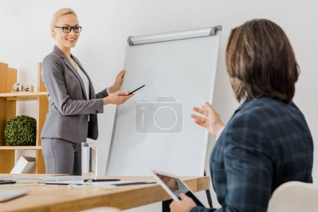 young smiling woman pointing at white board and man sitting at table with tablet in office