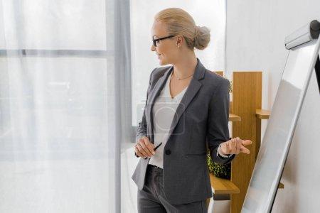Photo pour Jeune femme souriante dans des verres pointant sur tableau blanc au bureau - image libre de droit
