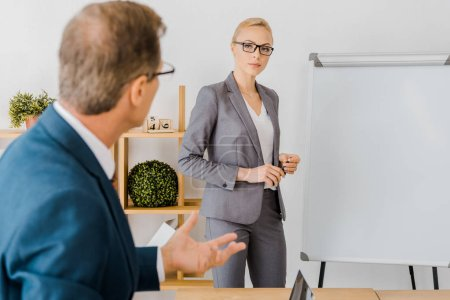 adult man talking to young woman near white board in office