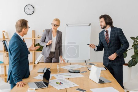 business people standing near table and having discussion in office