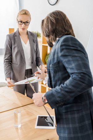 young woman and man standing at meeting in office
