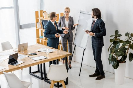 office workers standing near white board and having discussion