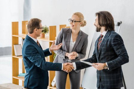 two businessmen shaking hands and talking to smiling businesswoman in office
