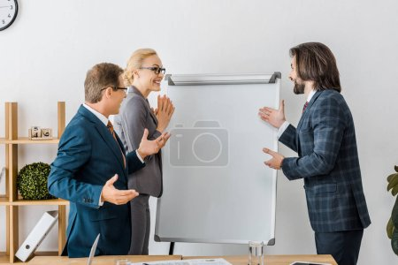 Photo for Smiling office workers pointing at white board at meeting - Royalty Free Image