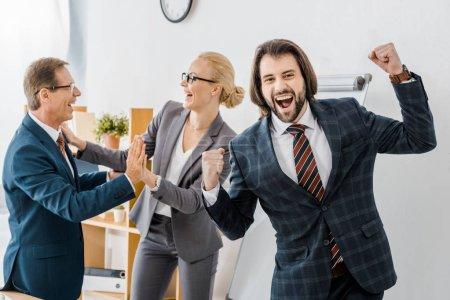 Photo pour Heureux agents d'assurance se réjouissant beaucoup dans le bureau - image libre de droit