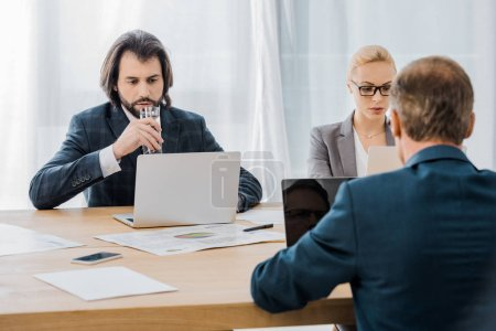 business people sitting at table with laptops in office