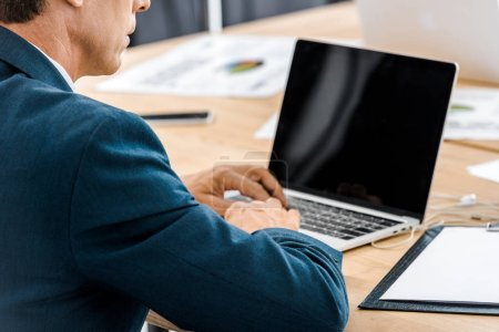 Adult businessman using laptop with blank screen in office