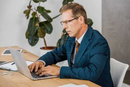 adult businessman in glasses using laptop in office