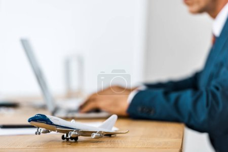 toy airplane at wooden table with office worker using laptop on blurred background