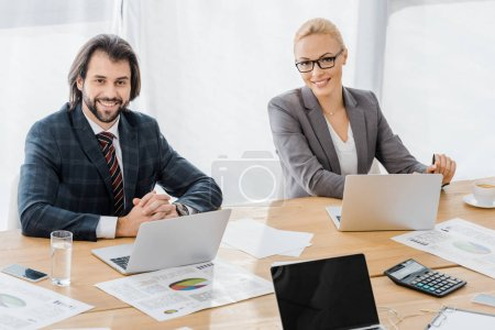 smiling business people sitting at table with laptops in office