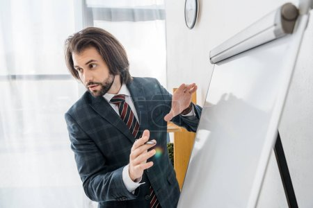 young businessman standing near white board in office and speaking during meeting
