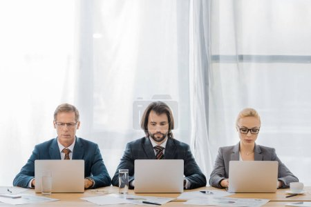 insurance workers sitting at table and using laptops in office