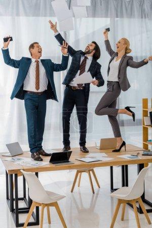 Photo pour Travailleurs d'assurance joyeuses danse sur la table et de jeter les papiers à la réunion dans le Bureau - image libre de droit