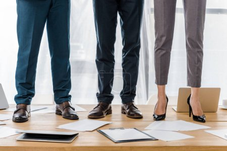 business people standing at wooden table in office