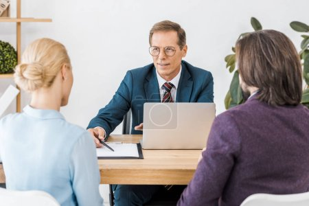 Photo for Adult insurance agent in glasses talking to young couple in office - Royalty Free Image