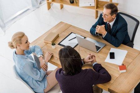 Photo pour Adulte agent d'assurance dans des verres parler jeune couple au bureau - image libre de droit