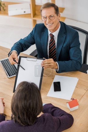adult smiling insurance agent in glasses showing contract to young man in office