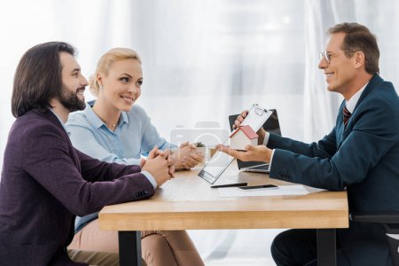 adult smiling insurance agent showing contract and house model to young couple in office