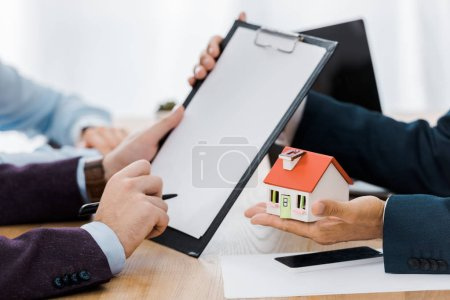 Photo for Man signing contract on clipboard while insurance agent holding house model - Royalty Free Image