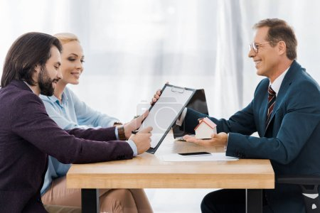 adult smiling insurance agent showing contract and small house to young couple in office