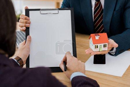 Photo pour Signature du contrat sur presse-papiers tandis que l'agent d'assurance détenant la maison modèle l'homme - image libre de droit