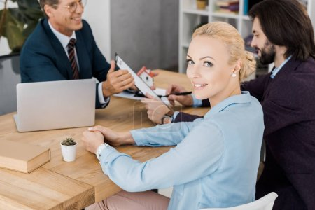 young smiling woman looking at camera while man signing contract with insurance agent