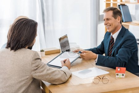 adult smiling insurance agent showing contract to man in office
