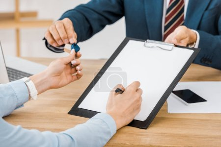 insurance agent giving keys and contract on clipboard to woman
