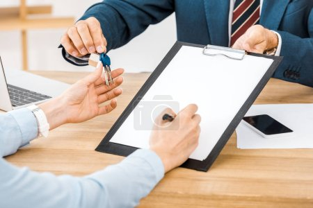 insurance agent giving keys and contract for signing on clipboard to woman
