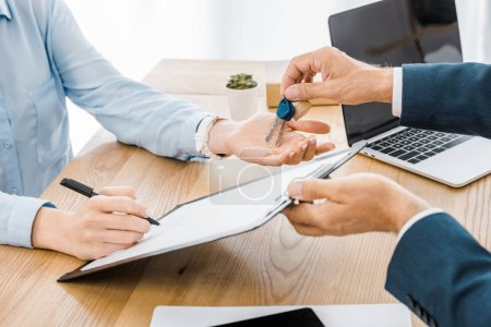 insurance agent holding keys while woman signing contract on clipboard