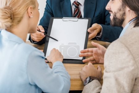 businessman showing contract on clipboard to couple