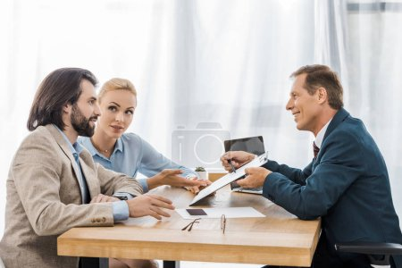 businessman showing contract on clipboard to couple for signing