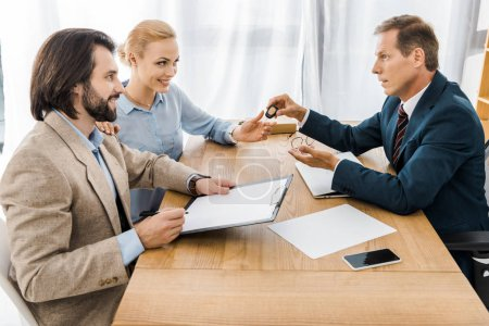 Photo for Insurance agent giving key to woman while man signing papers - Royalty Free Image