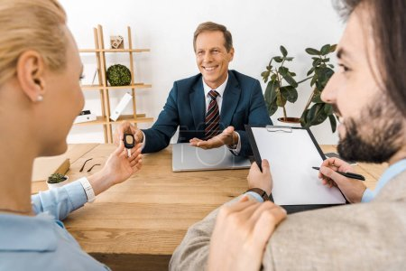 smiling businessman giving key to woman while man signing papers
