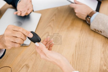 close up of man giving key to woman at wooden table