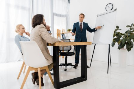 businessman pointing at white board while couple sitting in office