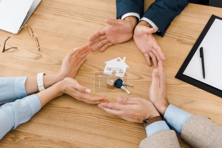 People making circle with hands on wooden table with paper house and keys inside, house insurance