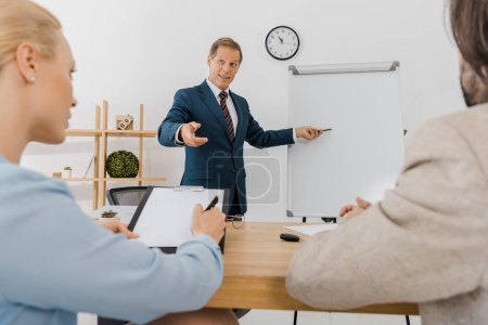 businessman pointing at white board while couple signing contract on clipboard