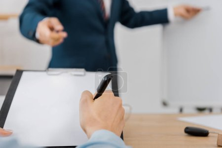 close up of man signing contract on clipboard while businessman standing near white board